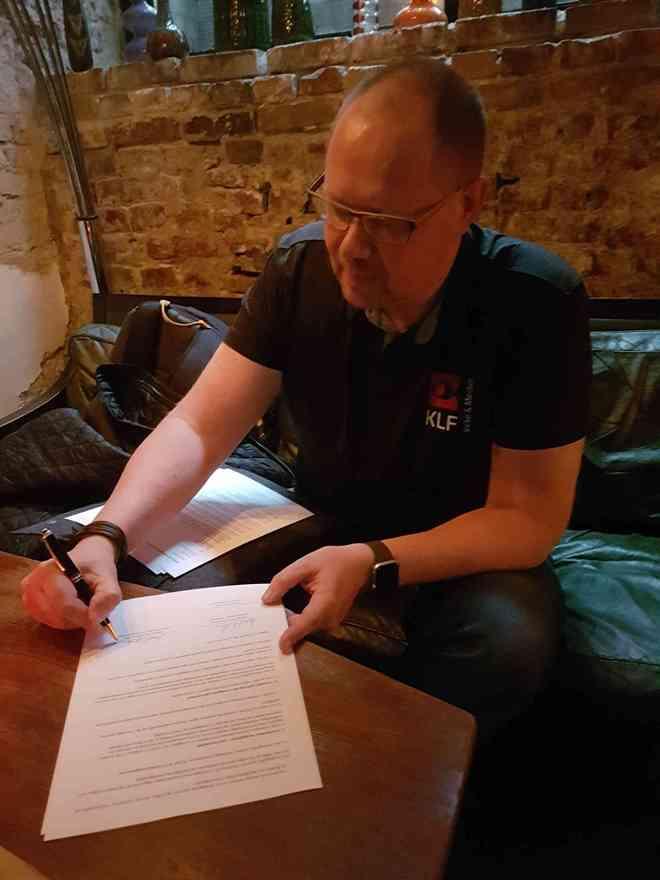 Generalsekretær Mikael Arendt Laursen skriver partnerskabsaftalen mellem FrikirkeNet og KLF, Kirke & Medier under